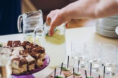 Hand taking glass of fresh lemonade at candy bar table with drin. Ks at wedding reception. luxury catering at restaurant Royalty Free Stock Image