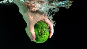 Hand taking green pepper from water Stock Image