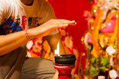 A hand taking heat of the flame as blessing from a lit clay lamp on top of a clay stand or worship idol durgapuja india diwali royalty free stock image