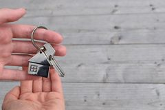 Hand taking house key from other person hand. Hand taking house key from realtor hand closeup view on blurred background. Real estate agent giving keys to Stock Photos