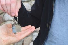 Hand taking house key from other person hand. Hand taking house key from realtor hand closeup view on blurred background. Real estate agent giving keys to Stock Photo