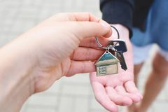 Hand taking house key from other person hand. Hand taking house key from realtor hand closeup view on blurred background. Real estate agent giving keys to Royalty Free Stock Image