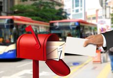 Hand taking a letter from a red postal box Stock Photography