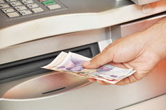 Hand taking money from ATM Stock Photo