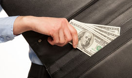 Hand taking money out of briefcase Stock Images