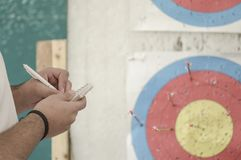 Hand taking note against an archery target Royalty Free Stock Images