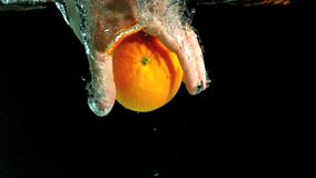 Hand taking orange from water Stock Photography