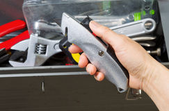 Hand taking out Box Cutter from toolbox Stock Photography