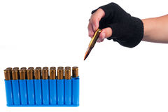 Hand taking out bullet Royalty Free Stock Images