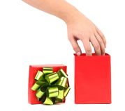 Hand taking out from green-golden bow. Royalty Free Stock Photos