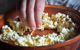 Hand taking out popcorn. From brown dish stock photography