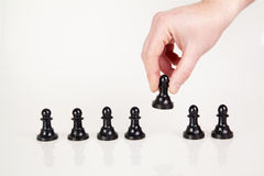 A hand taking pawn from the row. White background Stock Photography