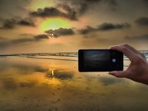 Hand taking photo of a beach sunset with smartphone stock image