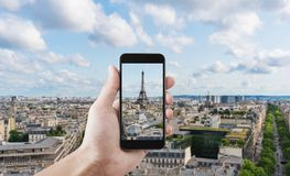 Hand taking photo of Eiffel tower, famous landmark and travel destination in Paris, France by mobile smart phone royalty free stock photography