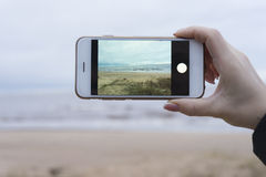 Hand taking photo with smart phone Royalty Free Stock Image
