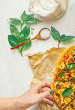 Hands taking slices of pizza. Hand holding slice pizza. Hand taking pizza slices from white wooden background. Pizza and hand close up over white background royalty free stock photography