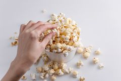 A hand is taking popcorn from a full paper bucket on a white background. Top view royalty free stock photo