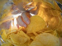Hand taking potato chips inside the bag.  stock photos