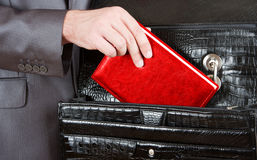 Hand taking red organizer from briefcase Stock Photography
