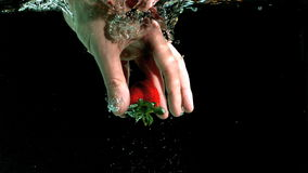 Hand taking strawberry from water Stock Photography