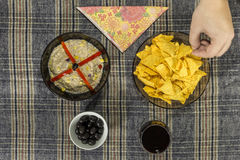 Hand taking a tortilla chips to dip in tuna salad Stock Image
