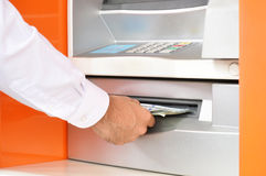 Hand taking (withdrawing) money from ATM Stock Photography