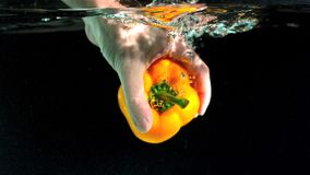 Hand taking yellow pepper from water Stock Photos