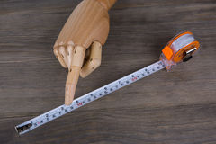 Hand and Tape measure, construction estimating tools. Hand and Tape measure on a wooden background. construction estimating tools Royalty Free Stock Photo