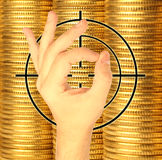 Hand and target against coins of yellow metal Stock Photos