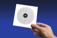Hand with target-card. Hand with a shooting-target isolated on blue, please take a look at my other images of targets Stock Photos