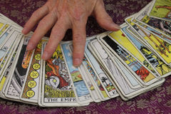 Hand on Tarot Cards. A hand moves over a selection of tarot cards that are spread out on a table royalty free stock photo