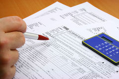 Hand and tax forms. Male hand about to fill out U.S. tax forms Stock Images