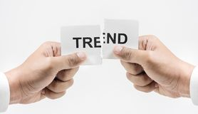 Hand tearing paper with TREND word in white tone background. Royalty Free Stock Photo