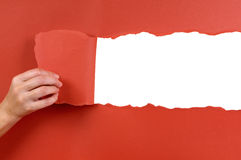 Hand tearing red paper background uncovering white copy space Royalty Free Stock Photo