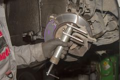 A hand technical specialist repairing the brake system of the modern car stock image