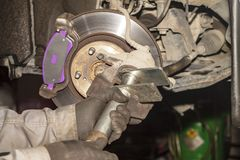 A hand technical specialist repairing the brake system of the modern car.  royalty free stock image