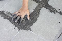 Technician sample wrong work on gray color of new grout tile. ฺhand of technician sample wrong work on gray color of new grout tile on tile gray for the final Royalty Free Stock Photography