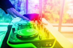 Hand of Technician using Sound system mixing audio equipment board on stage with soft light.DJ mixing sound in party at pub and. Bars with colorful effect royalty free stock photography