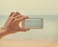 Hand with telephone - shooting seascape Stock Image