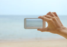 Hand with telephone - shooting seascape Royalty Free Stock Photo