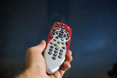 Hand the television remote control. The hand the television remote control, blue yellow backgraund royalty free stock photo