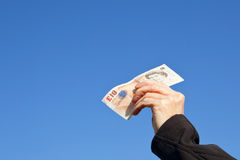 A hand with a ten pound note. A hand holding up a ten pound note against a clear blue sky stock image