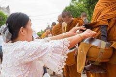 Hand terwijl het gezette voedseldienstenaanbod in de aalmoes van een Boeddhistische monnik werpt F Stock Fotografie