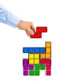 Hand with tetris toy blocks Stock Photo