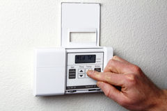 Hand on Thermostat. Fingers pushing control buttons on heating and cooling digital wall panel display Stock Photo