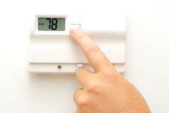 Hand and thermostat Stock Photos