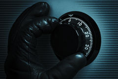 Hand of thief. Opens combination safe lock royalty free stock image