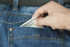 Hand Thief pulls the jeans with a dollar. Stealing money from the pocket of his jeans Stock Photo