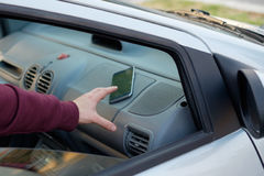 Hand of a thief stealing a mobile phone from a parked car. In the street stock image