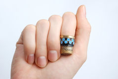 Hand, a thimble on her finger. Hand, a beautiful thimble on her finger Stock Image